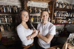 Porträt von stehenden Armen der überzeugten Paare kreuzte im Teespeicher Lizenzfreies Stockfoto