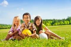 Porträt von thee glücklichen Kindern mit Bällen Lizenzfreie Stockbilder