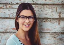 Porträt von tragenden Brillen der glücklichen Frau gegen hölzerne Wand Stockfotografie
