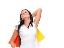 Porträt von tragenden Einkaufstaschen der jungen Frau gegen weißes BAC Lizenzfreie Stockbilder