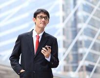 Porträt von tragenden Gläsern des jungen Geschäftsmannes und von mit smartpho Stockbild