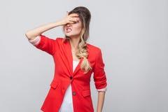 Porträt von traurigem verlieren schöne Geschäftsdame mit Frisur und Make-up im roten fantastischen Blazer und stehen, Hand auf ih lizenzfreie stockfotografie