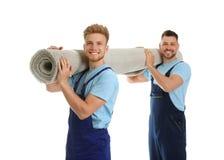 Porträt von umziehenden Service-Angestellten mit Teppich lizenzfreie stockbilder