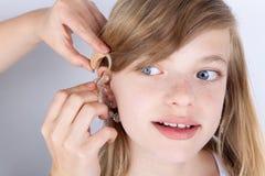 Porträt von versuchenden Hörgeräten eines jungen Mädchens lizenzfreie stockbilder