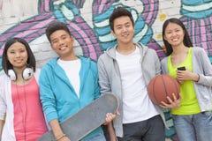 Porträt von vier Freunden, die ein Skateboard und einen Fußball heraus hängend vor einer Wand bedeckt in den Graffiti halten Stockfotografie