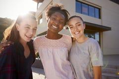 Porträt von weiblichen hohen Schüler-Friends Outside College-Gebäuden stockfotos