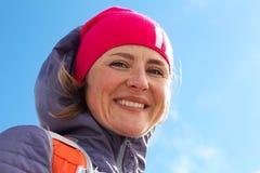 Porträt von Winterkleidung der jungen Frau und Stellung auf Berg und Lächeln an der Kamera Frau in der warmen Kleidung mit stockfotografie