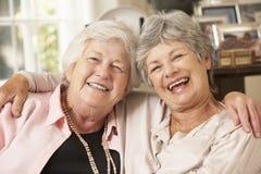 Porträt von zwei älteren Freundinnen im Ruhestand, die auf Sofa sitzen Stockfoto