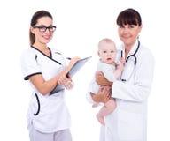 Porträt von zwei Ärztinkinderärzten mit dem kleinen Babypatienten lokalisiert auf Weiß stockfotos