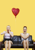 Porträt von zwei überraschte die jungen Frauen, die auf Sofa mit Herz geformtem Ballon über gelbem Hintergrund sitzen Stockbild