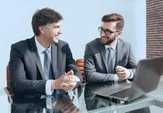 Porträt von zwei Geschäftsleuten, die am Schreibtisch sitzen Lizenzfreies Stockbild