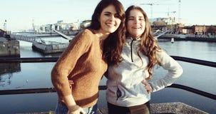 Porträt von zwei glücklichen Jugendlichfreunden, die zur Kamera mit Lächeln vor Drogheda-Fluss umarmen und schauen Geschossen auf stock video