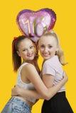Porträt von zwei glücklichen jungen Frauen mit dem Geburtstagsballon, der über gelbem Hintergrund umarmt Stockfoto