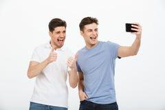 Porträt von zwei glücklichen jungen Männern, die Finger zeigen Lizenzfreies Stockfoto
