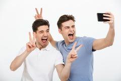 Porträt von zwei glücklichen jungen Männern, die Frieden zeigen, gestikulieren Lizenzfreie Stockfotografie