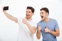 Porträt von zwei glücklichen jungen Männern, die sich Daumen zeigen Lizenzfreie Stockbilder