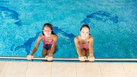 Porträt von zwei glücklichen lächelnden Jugendlichen im zuhause Swimmingpool lizenzfreie stockfotografie