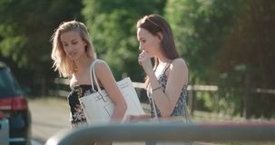 Porträt von zwei glücklichen Mädchen, die späteste Klatschnachrichten beim Gehen in einer Stadtstraße besprechen Stockfoto