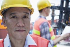 Porträt von zwei Ingenieuren in der schützenden Arbeitskleidungsfunktion, Kamera betrachtend, Außenseite in einem Versandyard Lizenzfreies Stockfoto