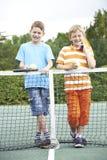 Porträt von zwei Jungen, die zusammen Tennis spielen lizenzfreie stockfotos