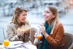 Porträt von zwei jungen Frauen, die draußen Pizza essen lizenzfreie stockfotos