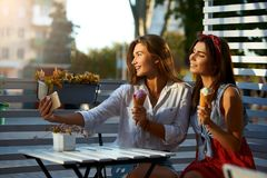 Porträt von zwei jungen Frauen, die Eistüten sitzen zusammen, essend und selfie Foto herein machend auf Mobiltelefonkamera stockbild