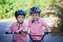 Porträt von zwei Jungen im Park, im Reitenfahrrad und im Roller Stockbild