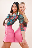 Porträt von zwei jungen Schönheiten blond u. von Brunette mit dem langen Haar u. identischer Kamera der Kostüme glückliches Lächel lizenzfreies stockbild