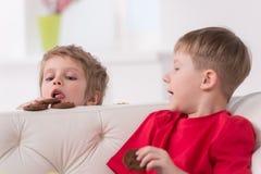 Porträt von zwei Kindern, die im weißen Sofa essen Stockfoto