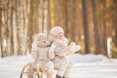 Porträt von zwei kleinen Mädchen sitzen auf einem Schlitten und einem Spiel mit Schnee im Winter Stockbilder