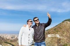 Porträt von zwei lächelnden jungen Männern, die selfi im Berg machen Lizenzfreie Stockbilder
