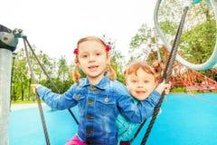 Porträt von zwei Mädchen auf Schwingen stellte in Sommer ein Stockfoto