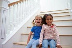 Porträt von zwei Mädchen, die zu Hause Spiel auf Treppenhaus spielen lizenzfreie stockfotografie
