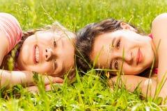 Porträt von zwei Mädchen, die zusammen auf Gras legen Stockfotografie