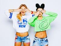 Porträt von zwei Mädchen moderne Blondine und Brunette, die ihre Augen durch Hände versteckt Zeigen der perfekten Maniküre tragen Stockfotografie