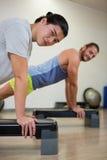 Porträt von zwei Männern, die Aerobic-Übung auf Stepper tun Stockbild