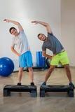 Porträt von zwei Männern, die Aerobic-Übung mit Stepper tun Stockfoto