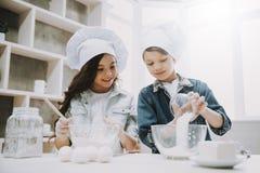 Porträt von zwei netten Kindern, die an der Küche kochen stockbilder