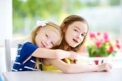 Porträt von zwei netten kleinen Schwestern zu Hause am schönen Sommertag stockfotos