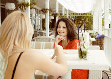 Porträt von zwei recht modernen Freundinnen bei dem Caféfreilicht-Innentrinken und der Unterhaltung, Chat und coctail habend Stockfotos