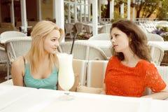 Porträt von zwei recht modernen Freundinnen bei dem Caféfreilicht-Innentrinken und der Unterhaltung, Chat und coctail habend Stockbild
