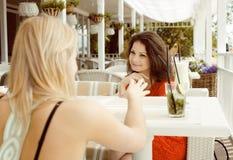 Porträt von zwei recht modernen Freundinnen bei dem Caféfreilicht-Innentrinken und der Unterhaltung, Chat und coctail habend Lizenzfreies Stockbild