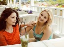 Porträt von zwei recht modernen Freundinnen bei dem Caféfreilicht-Innentrinken und der Unterhaltung, Chat und coctail habend Lizenzfreie Stockfotografie