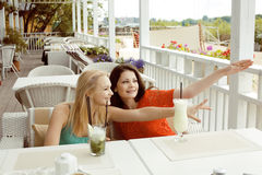 Porträt von zwei recht modernen Freundinnen bei dem Caféfreilicht-Innentrinken und der Unterhaltung, Chat und coctail habend Lizenzfreie Stockbilder