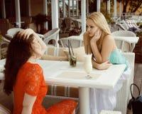 Porträt von zwei recht modernen Freundinnen bei dem Caféfreilicht-Innentrinken und der Unterhaltung, Chat und coctail habend Stockfotografie