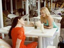 Porträt von zwei recht modernen Freundinnen bei dem Caféfreilicht-Innentrinken und der Unterhaltung, Chat und coctail habend Lizenzfreies Stockfoto