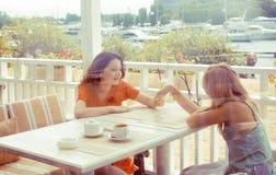 Porträt von zwei recht modernen Freundinnen bei dem Caféfreilicht-Innentrinken und der Unterhaltung, Chat und coctail habend Stockfoto