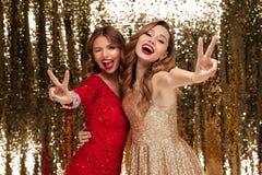 Porträt von zwei regte heitre Frauen in den sparkly Kleidern auf Stockfotos