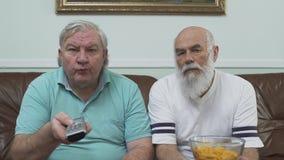 Porträt von zwei reifen älteren Männern, die auf dem braunen ledernen Sofa fernsieht sitzen Ein Mann, der die Schüssel mit Chips  stock footage