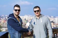 Porträt von zwei schönen jungen Männern, die Hände rütteln Stockfoto